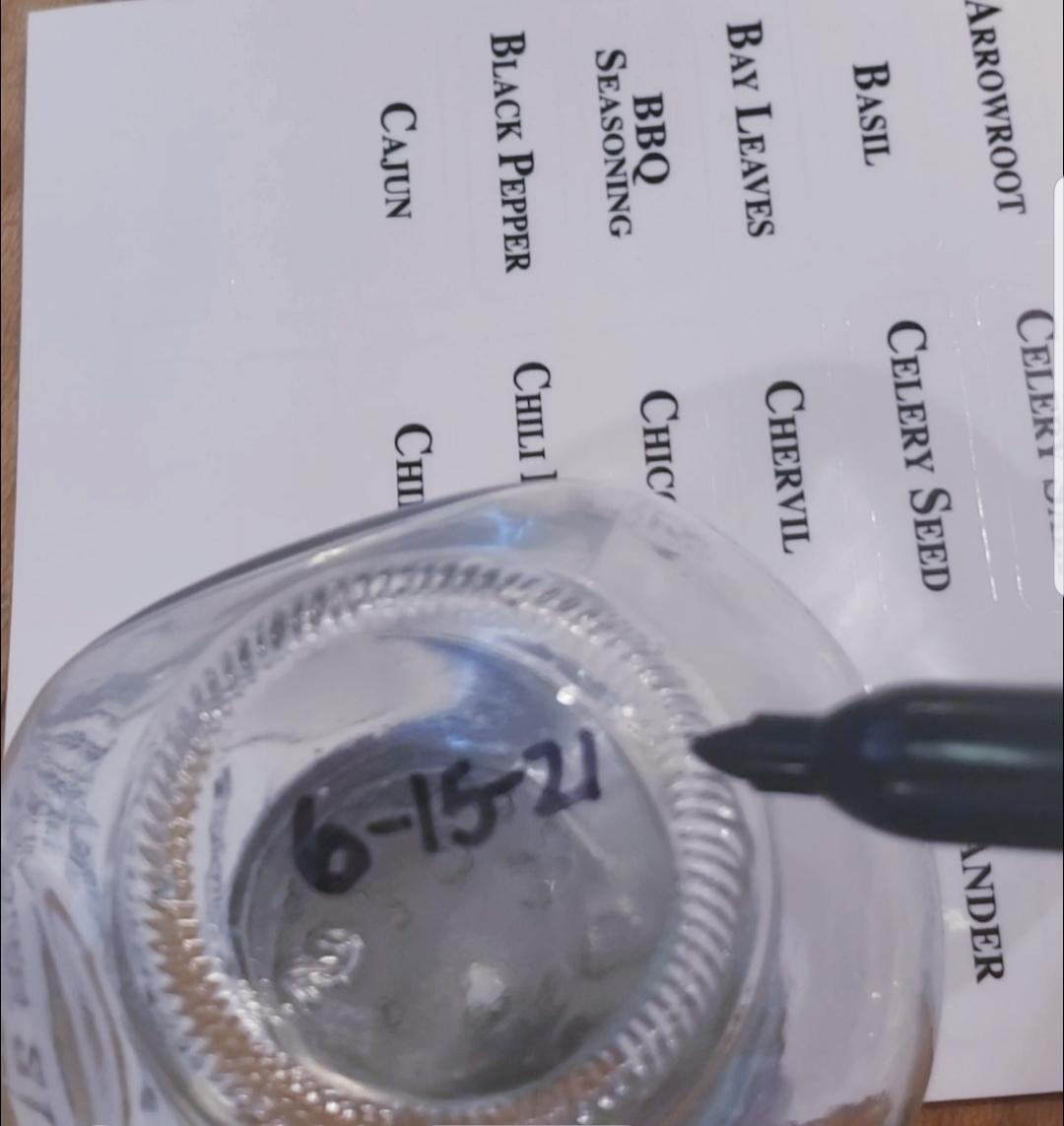 writing of expiration date of spices on bottom of jar